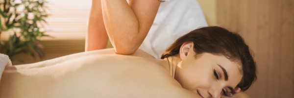 woman lying on the stomach receiving a deep tissue massage
